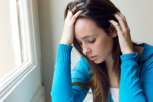 Portrait of depressed young woman sitting at home.